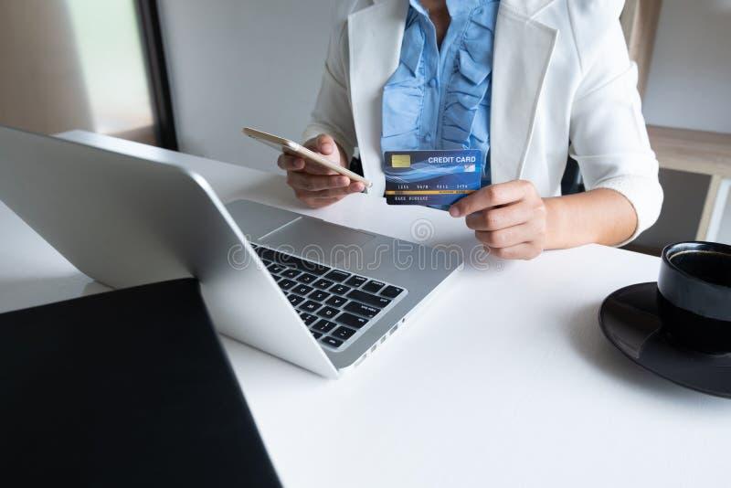 Kobieta używa kartę kredytową dla online zakupy na jej telefonie i laptopie obraz stock