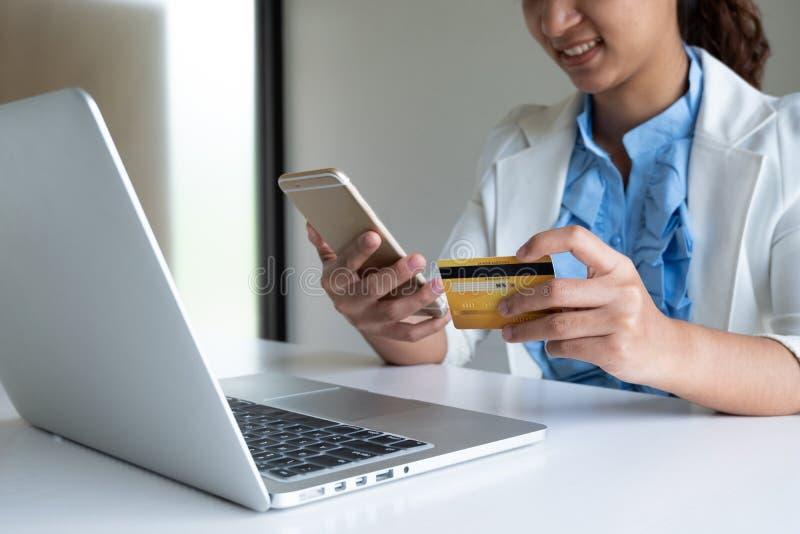Kobieta używa kartę kredytową dla online zakupy na jej telefonie i laptopie zdjęcie royalty free