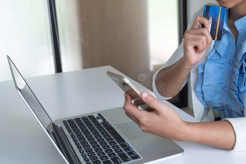 Kobieta używa kartę kredytową dla online zakupy na jej telefonie i laptopie fotografia stock