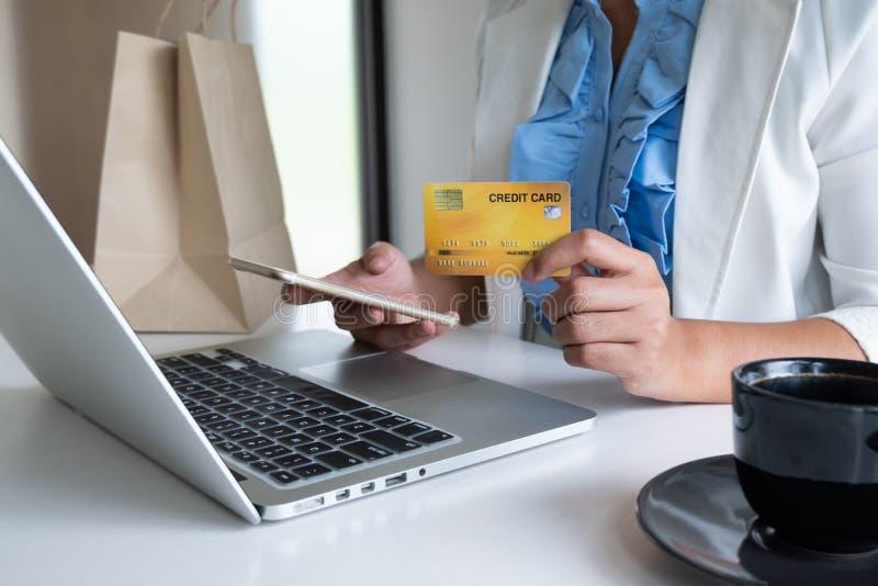 Kobieta używa kartę kredytową dla online zakupy na jej telefonie i laptopie obrazy royalty free