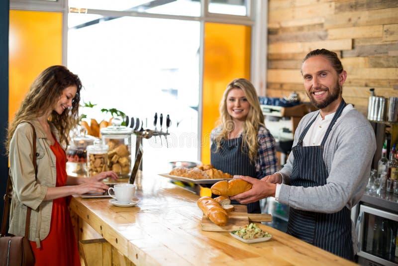 Kobieta używa laptopu i kelnera tnącego chleb przy kontuarem obrazy stock
