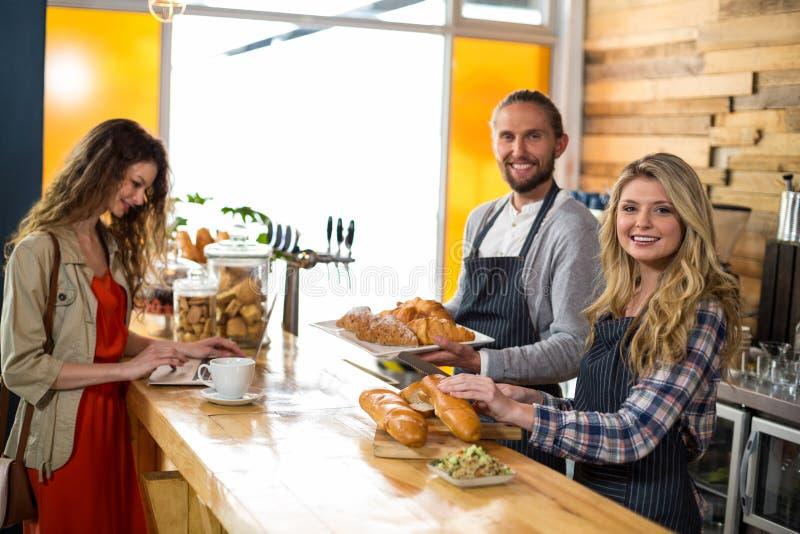 Kobieta używa laptopu i kelnera tnącego chleb przy kontuarem fotografia stock