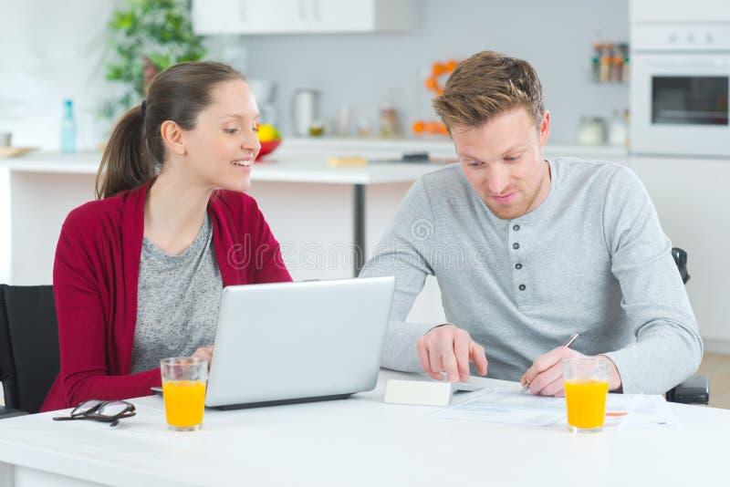 Kobieta używa laptopu mężczyzny robi notatkom na prześcieradło papierze obrazy royalty free