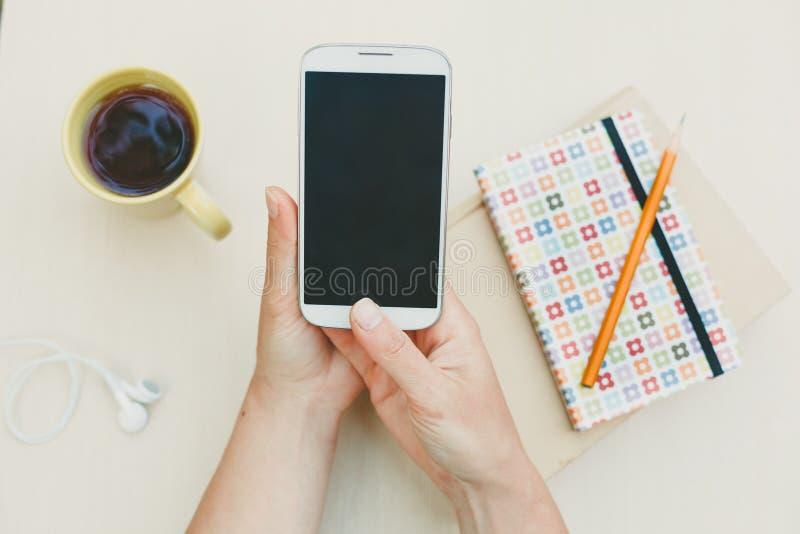 Kobieta używa mądrze telefon na stole zdjęcia stock