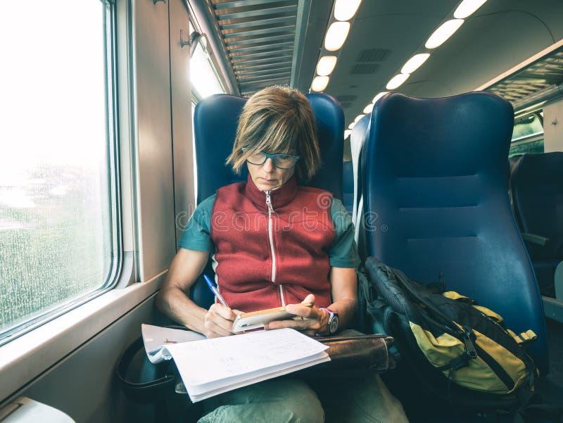 Kobieta używa mądrze telefon siedzi podróżować taborowym ręki writing na papierze Desaturated zimny brzmienie koloru oceniać Prac obraz stock