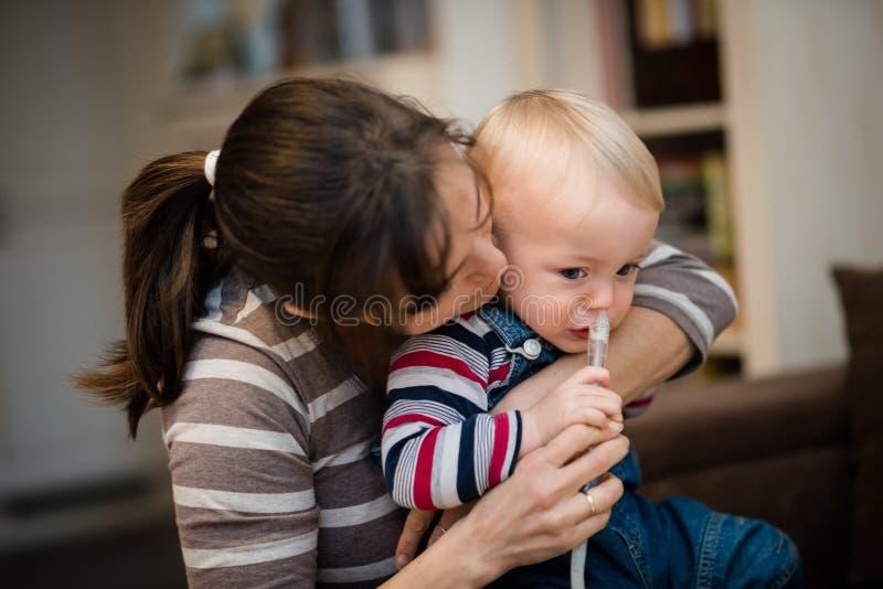 Kobieta używa nosowego aspirator dla dziecka zdjęcia stock