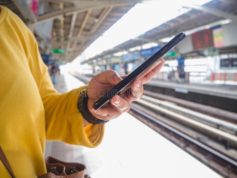 Kobieta używa palcowego dotyka na ekranie telefon komórkowy na BTS nieba pociągu tle obrazy royalty free