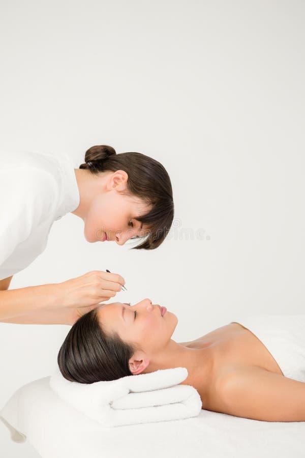 Kobieta używa pincety na cierpliwej brwi zdjęcie stock