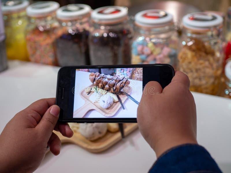 Kobieta używa smartphone fotografii cukierki dla ogólnospołecznych sieci w kawiarni Ostrość mobilny pokaz podczas gdy strzelający zdjęcie royalty free