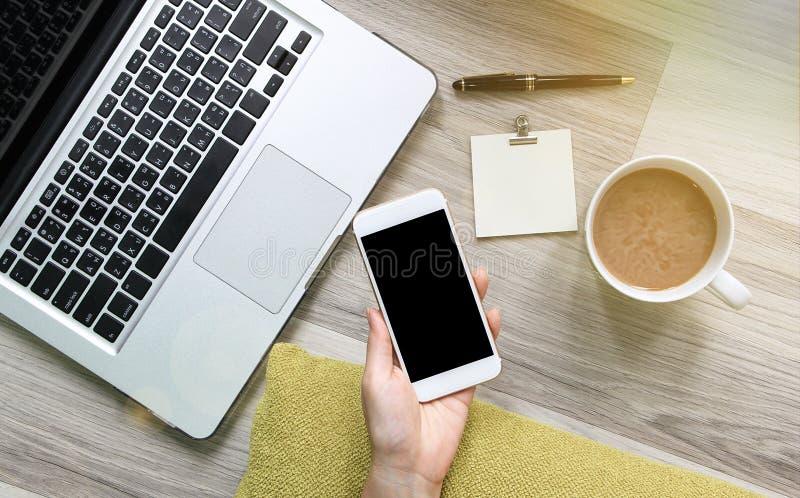 Kobieta używa smartphone i laptop na drewnianej podłoga obrazy stock
