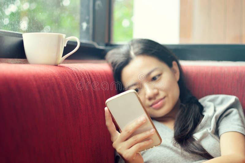 Kobieta używa smartphone na leżance fotografia royalty free