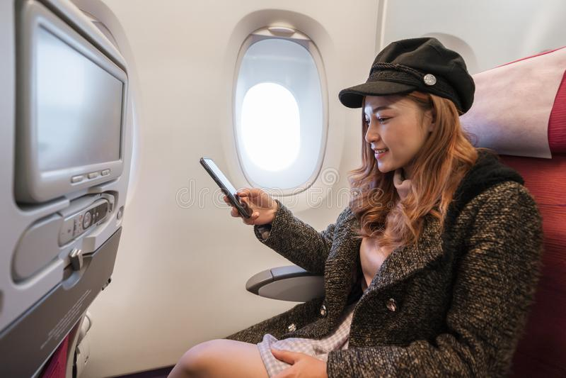 Kobieta u?ywa smartphone w samolocie w lota czasie zdjęcia royalty free