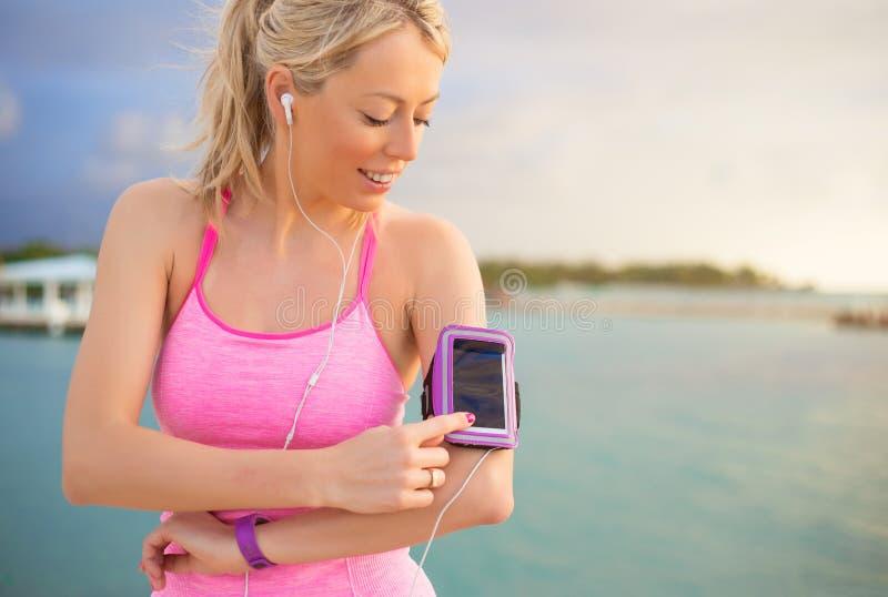 Kobieta używa sporty tropi wiszącą ozdobę app na jej smartphone obraz royalty free