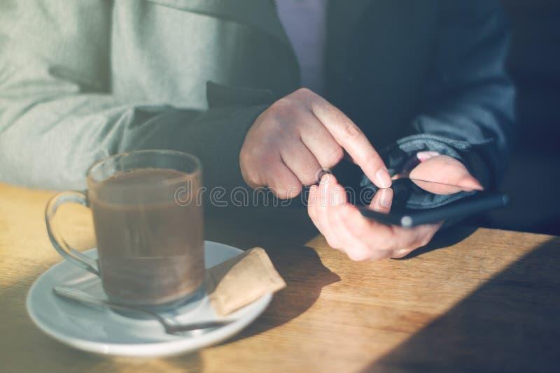 Kobieta używa telefon komórkowego i pijący gorącą czekoladę w kawiarni zdjęcia stock