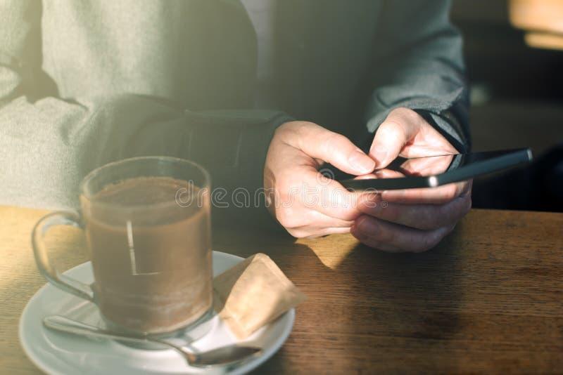 Kobieta używa telefon komórkowego i pijący gorącą czekoladę w kawiarni obrazy royalty free