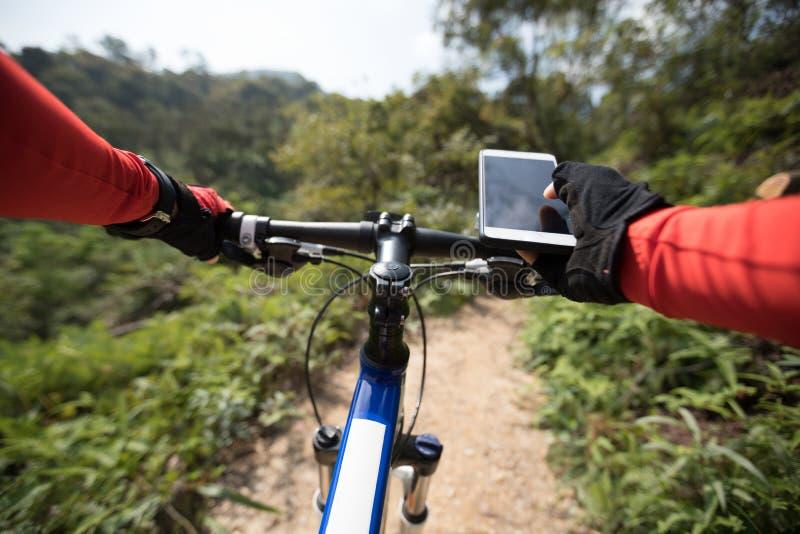 Kobieta używa telefon komórkowego jechać na rowerze podczas gdy jeździecki obraz stock