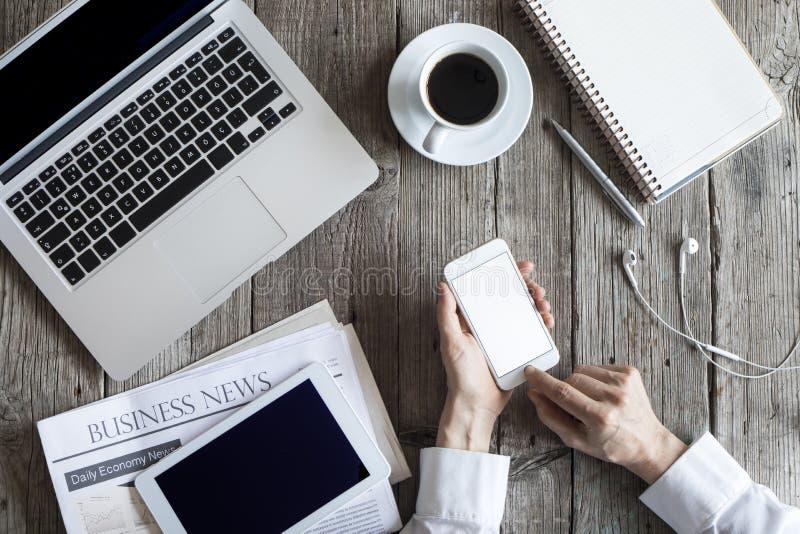 Kobieta używa telefon komórkowego na pracującym stole obraz royalty free