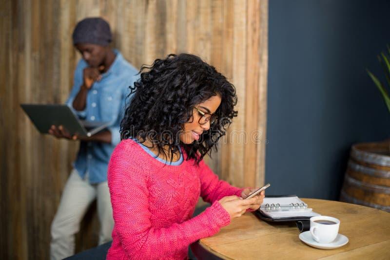 Kobieta używa telefon komórkowego podczas gdy mieć kawę w café obraz royalty free