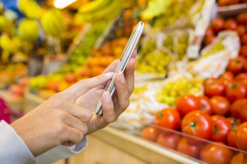 Kobieta używa telefon komórkowego w supermarkecie podczas gdy robiący zakupy zdjęcie royalty free