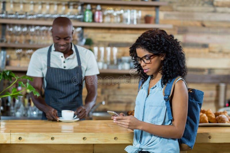 Kobieta używa telefon komórkowego w tle podczas gdy kelner pozycja zdjęcie stock