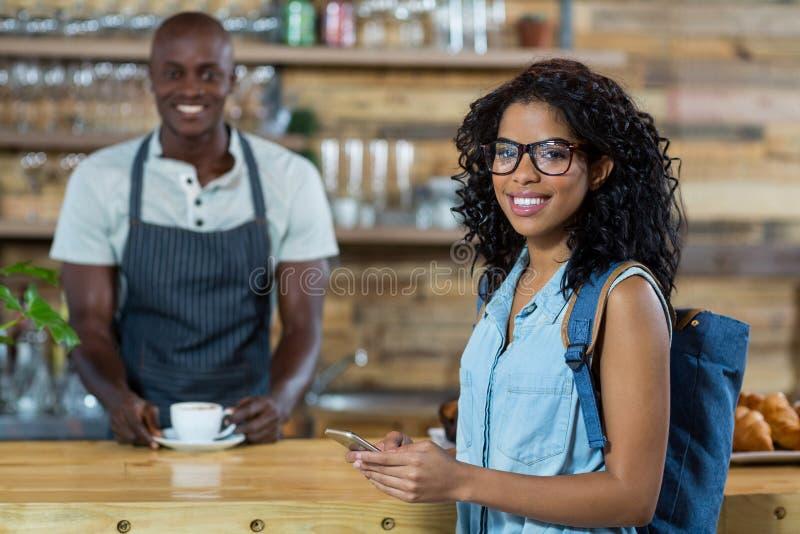 Kobieta używa telefon komórkowego w tle podczas gdy kelner pozycja zdjęcia royalty free