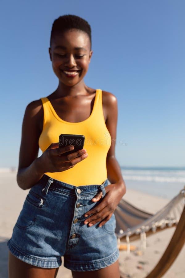 Kobieta używa telefon komórkowego z jej kciukami w pasku zapętla na plaży zdjęcia royalty free