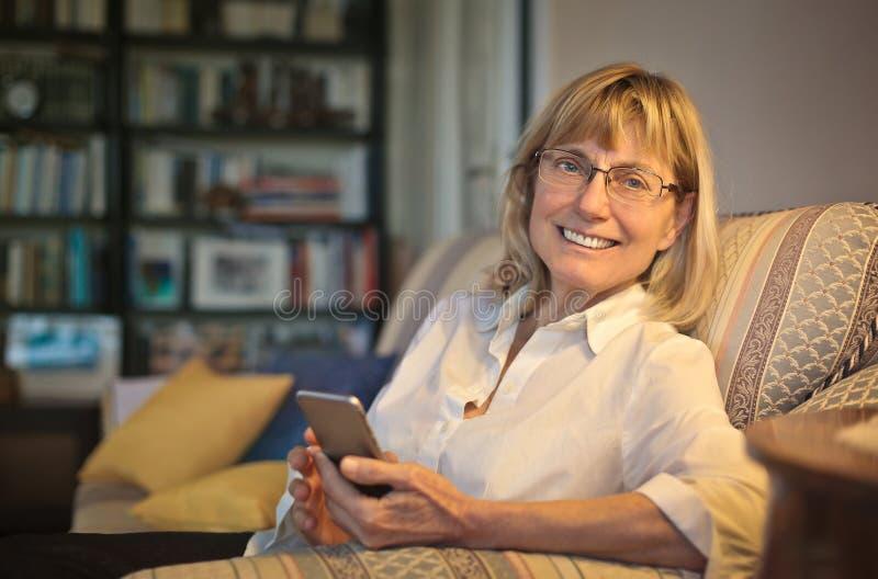 Kobieta używa telefon w leżance zdjęcie stock