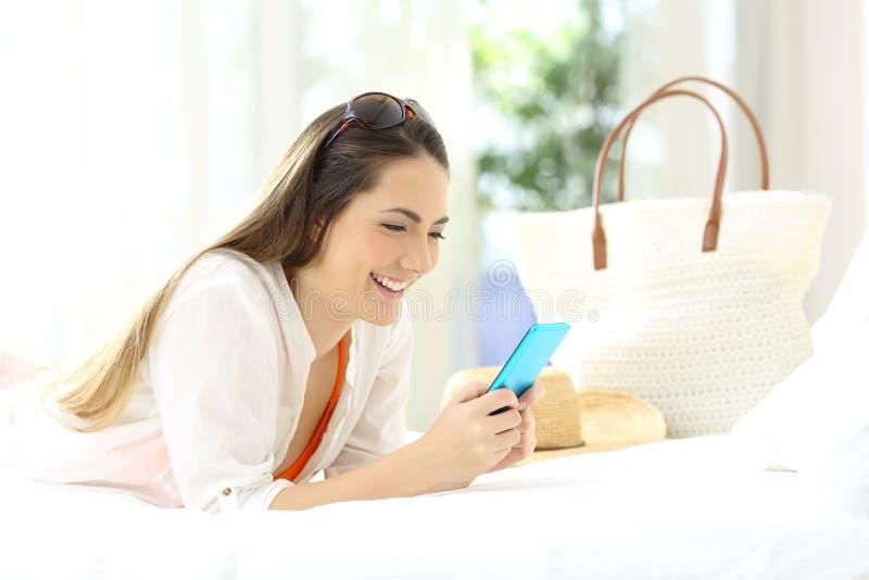 Kobieta używa telefon w pokoju hotelowym na wakacjach obrazy royalty free