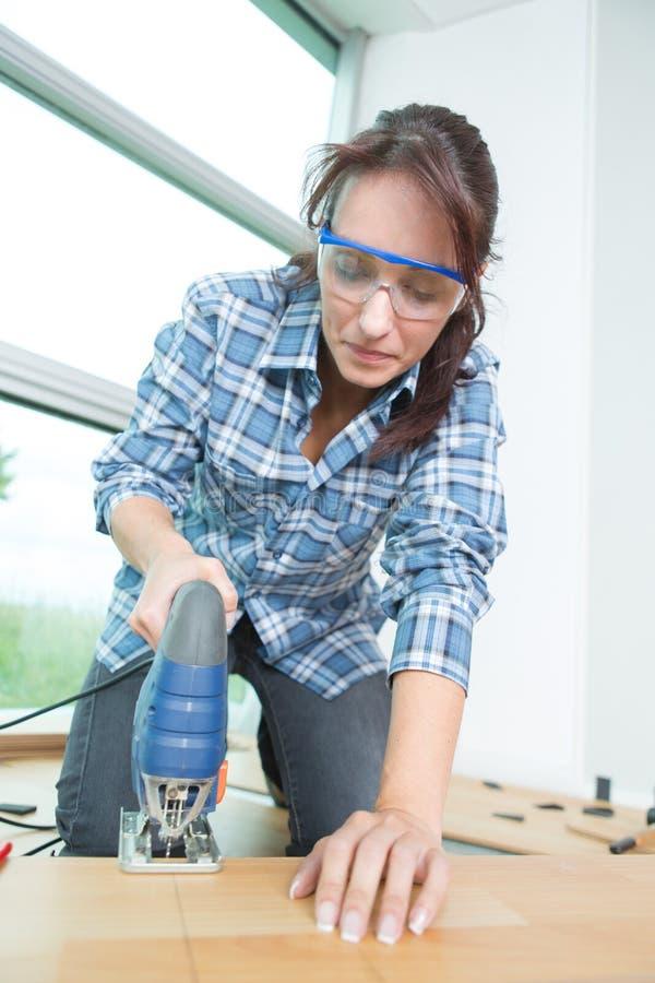 Kobieta używająca narzędzi stolarki na drewnianym podłodze obrazy stock