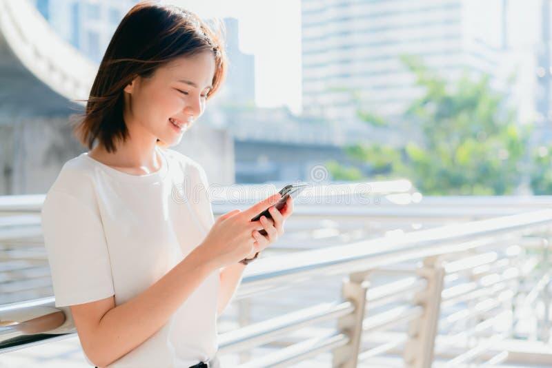 Kobieta u?ywa smartphone, Podczas wolnego czasu Poj?cie u?ywa? telefon jest istotny w ?yciu codziennym obraz royalty free