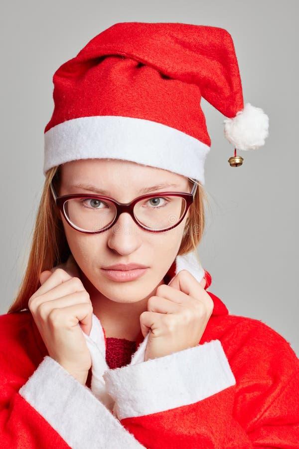Kobieta ubierał jako Święty Mikołaj z poważnym spojrzeniem obrazy stock