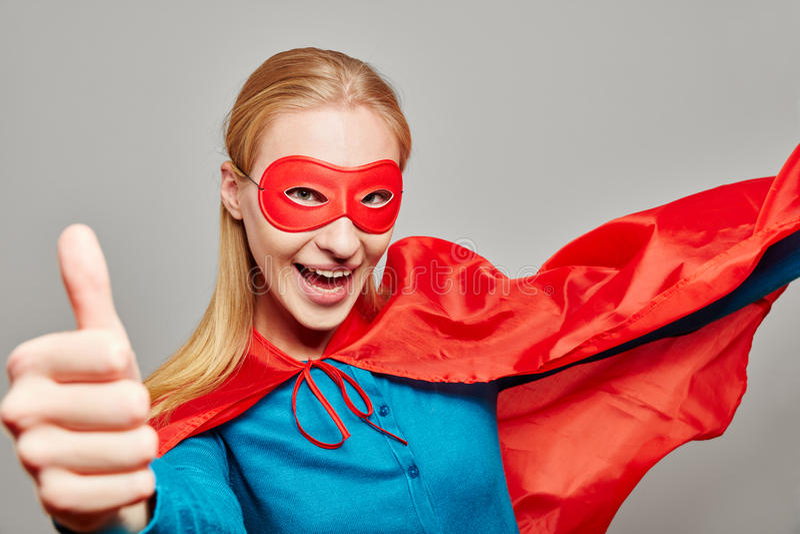 Kobieta ubierał jako bohater z jej kciukiem up obrazy stock