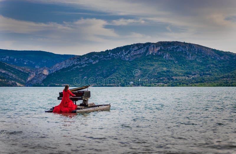 Kobieta ubierał w czerwieni bawić się pianino na jeziorze obraz royalty free