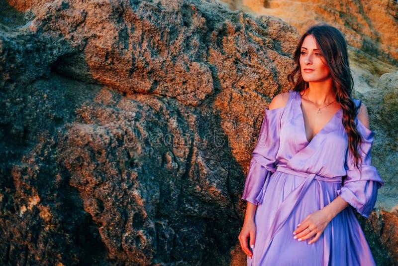 Kobieta ubierał w jedwabniczej purpurowej spływanie sukni pozycji przy skałą zdjęcie stock