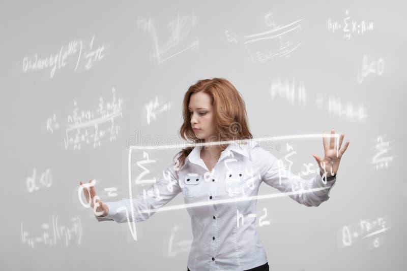 Kobieta uczeń lub pracuje różnorodnymi szkół średnich maths i nauki formułą obraz stock
