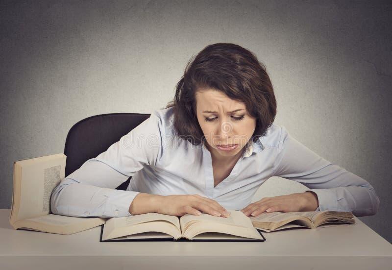 Kobieta uczeń z desperacki wyrażeniowym patrzejący jej książki fotografia stock