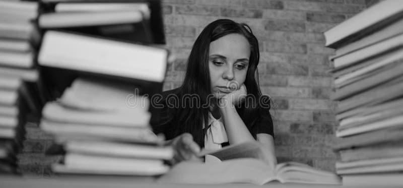 Kobieta uczeń zanudza czytelniczą książkę przy biblioteką z mnóstwo książkami w uniwersytecie Uczeń zniechęcająca czytelnicza ksi obraz royalty free