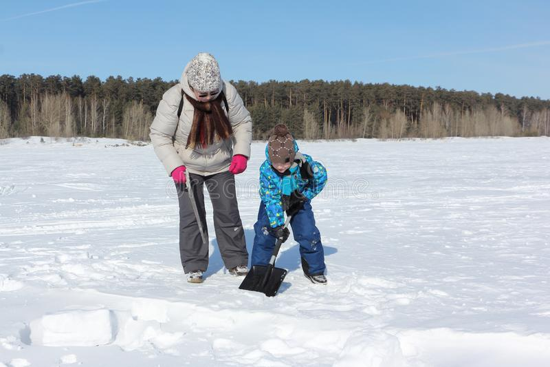 Kobieta uczy chłopiec kopać śnieżnego blok budować igloo, Novosibirsk, Rosja fotografia stock