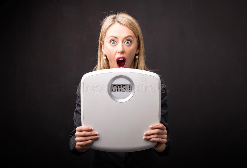 Kobieta udaremniająca ciężarem waży fotografia stock