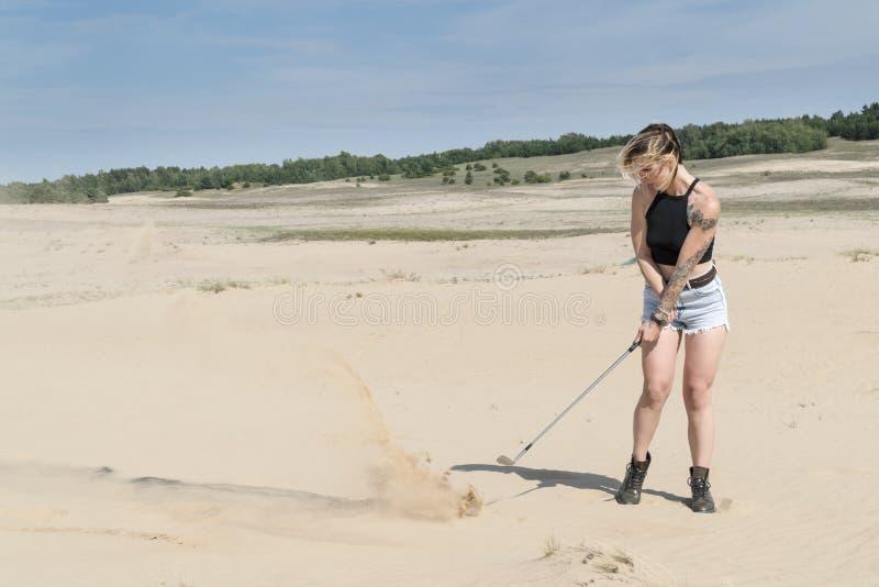 Kobieta uderza z kijem golfowym fotografia royalty free