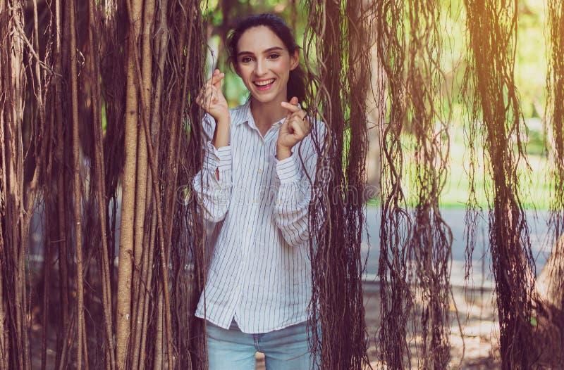 Kobieta ufności stojąca i pokazująca dłonie miłość do kształtu, szczęśliwy i uśmiechnięty, pozytywne myślenie, czas relaksu zdjęcia stock