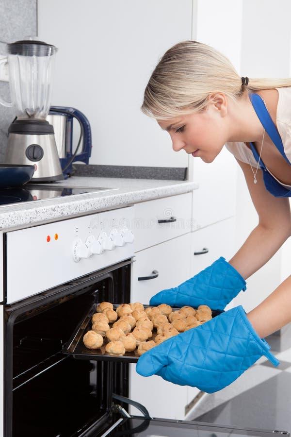 Kobieta Umieszcza ciastka W piekarniku obrazy royalty free