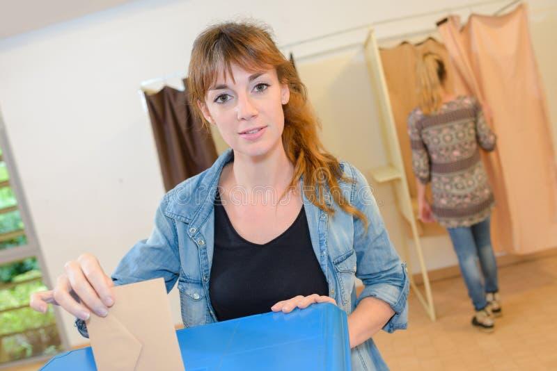 Kobieta umieszcza głosujący kopertę w łzawicę obraz stock