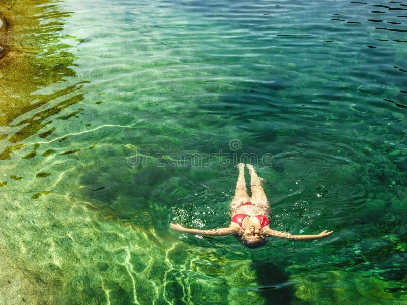 Kobieta unosi się w jasnej wodzie halna rzeka zdjęcie royalty free