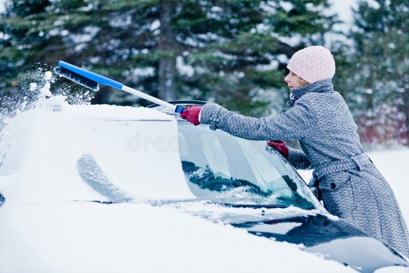 Kobieta Usuwa śnieg od samochodu z miotłą zdjęcie stock