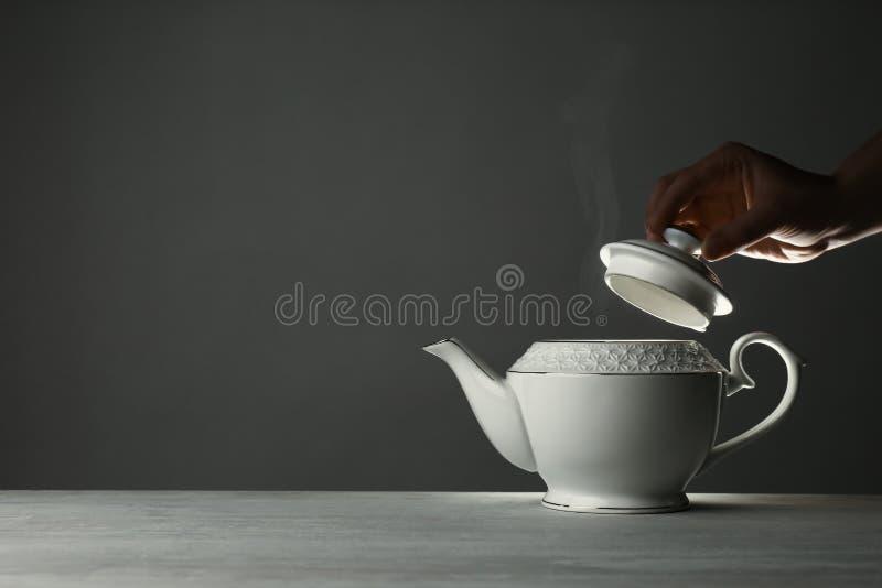 Kobieta usuwa dekiel od ceramicznego teapot przy stołem przeciw popielatemu tłu, zbliżenie obrazy royalty free