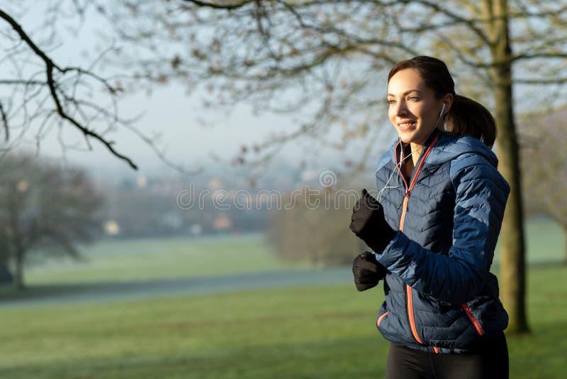 Kobieta Utrzymuje Dysponowanego słuchanie muzyka Przez słuchawek Na wczesny poranek zimy bieg W parku zdjęcia stock