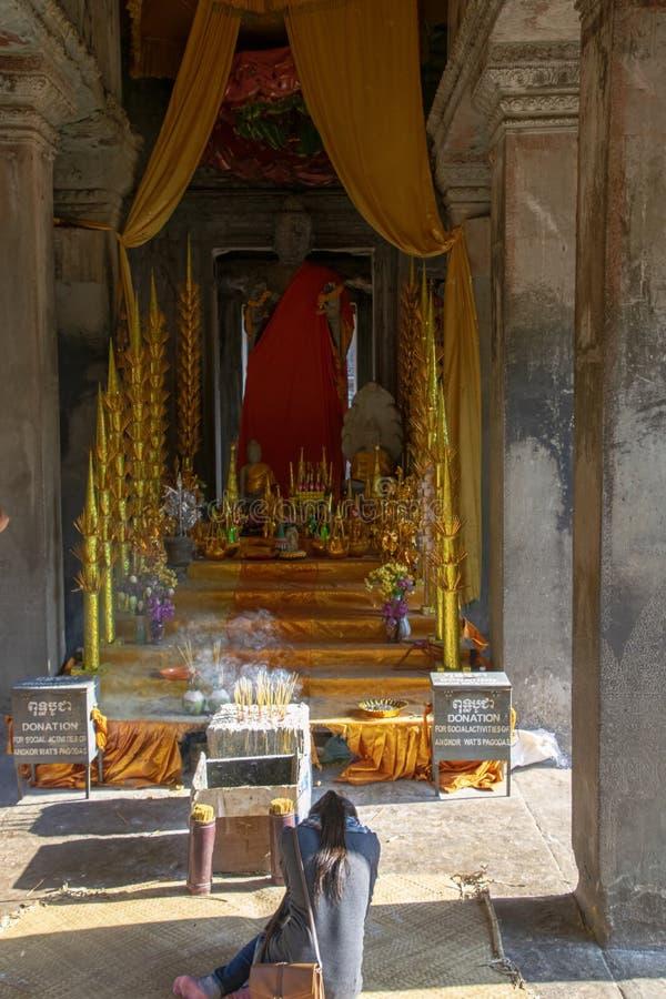 Kobieta uwielbia przy Antyczną Buddha statuą wśród Angkor Wat zdjęcia stock