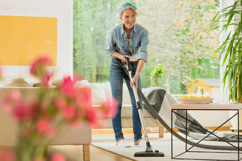 Kobieta vacuuming beżowego dywan fotografia royalty free