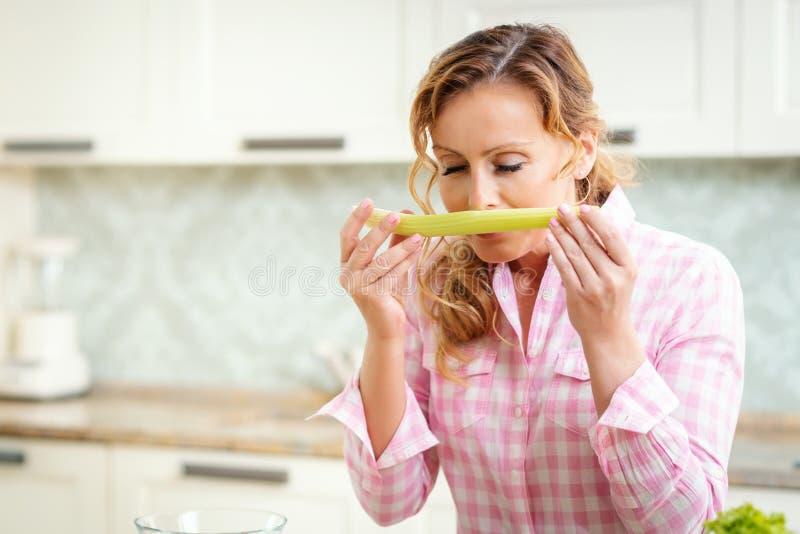 Kobieta wącha świeżego seleru w kuchni obrazy royalty free